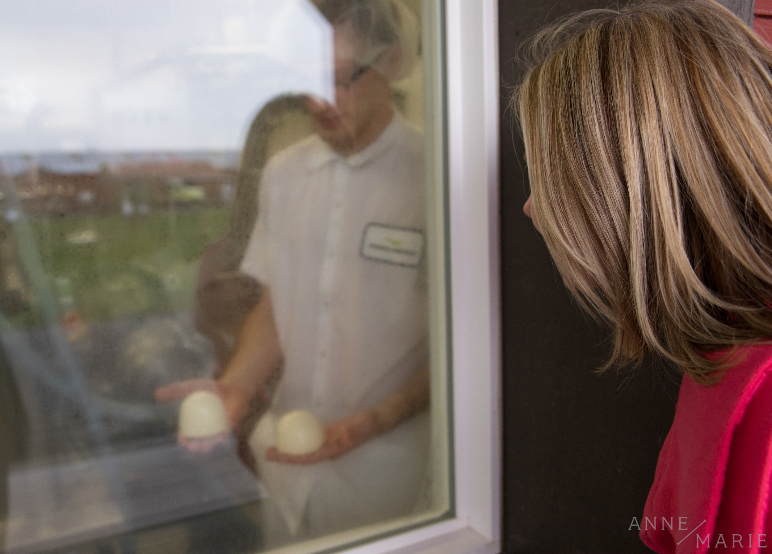 Daniel shows Anne-Marie fresh cheese through a window.