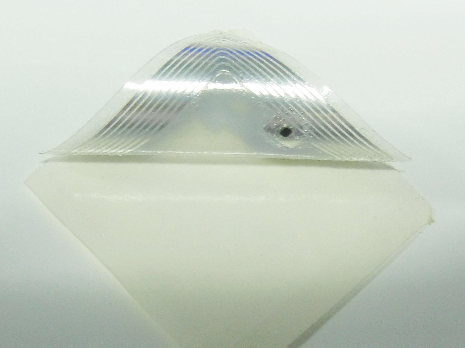Aluminum - Lifting an NFC tag reveals the aluminum antenna and NFC chip