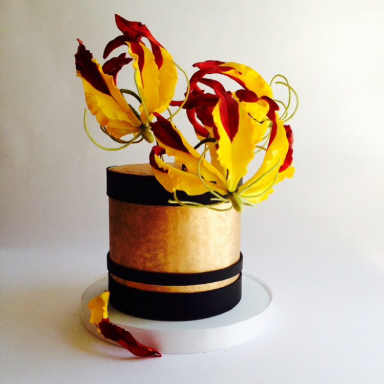 Fire.  Golden Birthday cake with Gloriosa Lilies