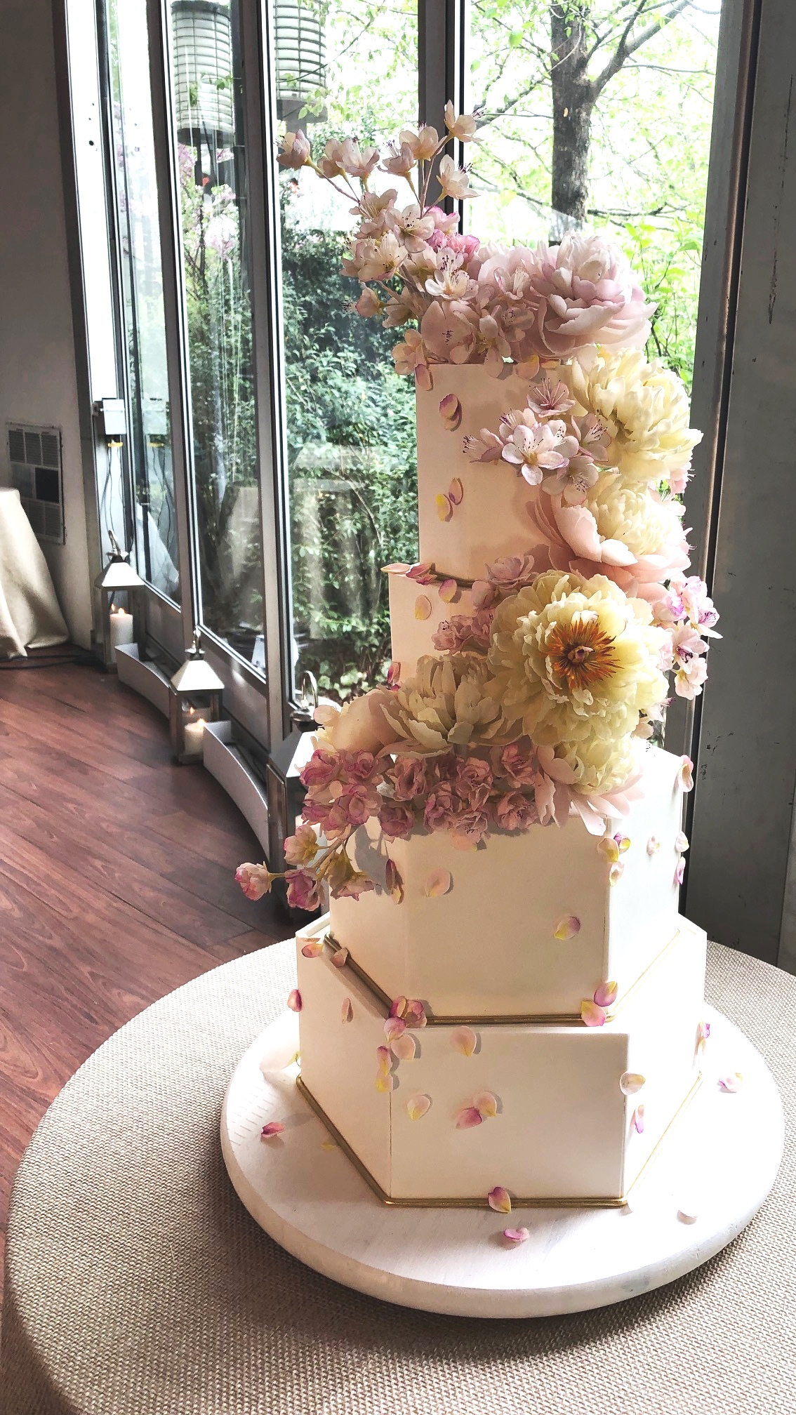 Soft and sharp are the lines of this wedding cake.  Sharp and perfectly sculpted corners of these hexagon tiers is balanced by soft sugar peonies and sugar cherry blossom.  A cascade of loose petals adds romance and organic vibes!