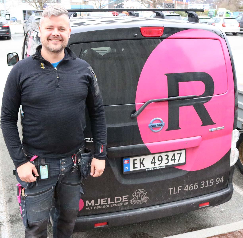 Rørleggermester Roger mjelde i positur foran en av bilene som ferdes rundt i Bergen