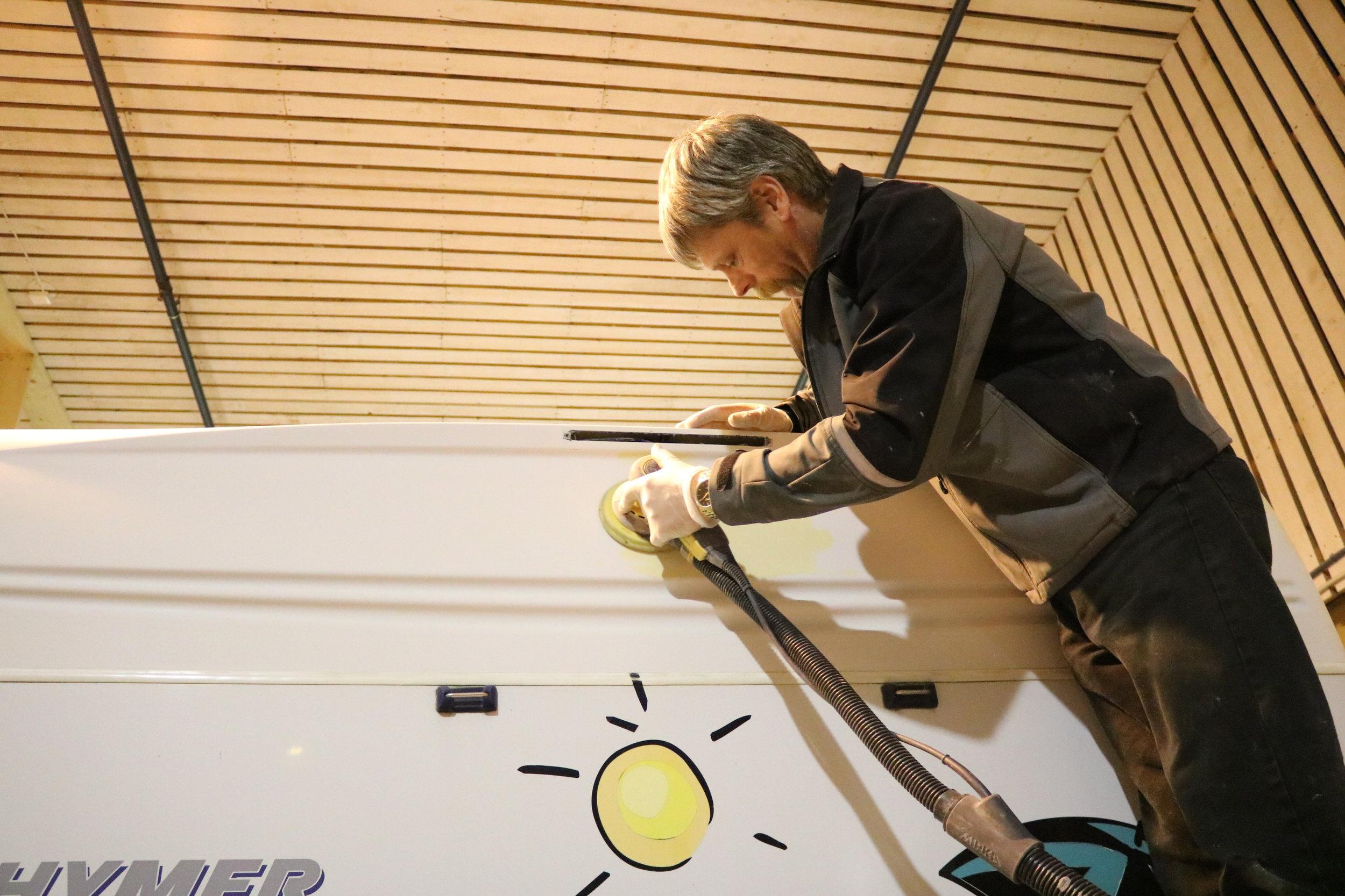 Her har Lars Erik tettet noen hull i bakenden av en bobil og er i gang med å pusse og legge siste finish på jobben.