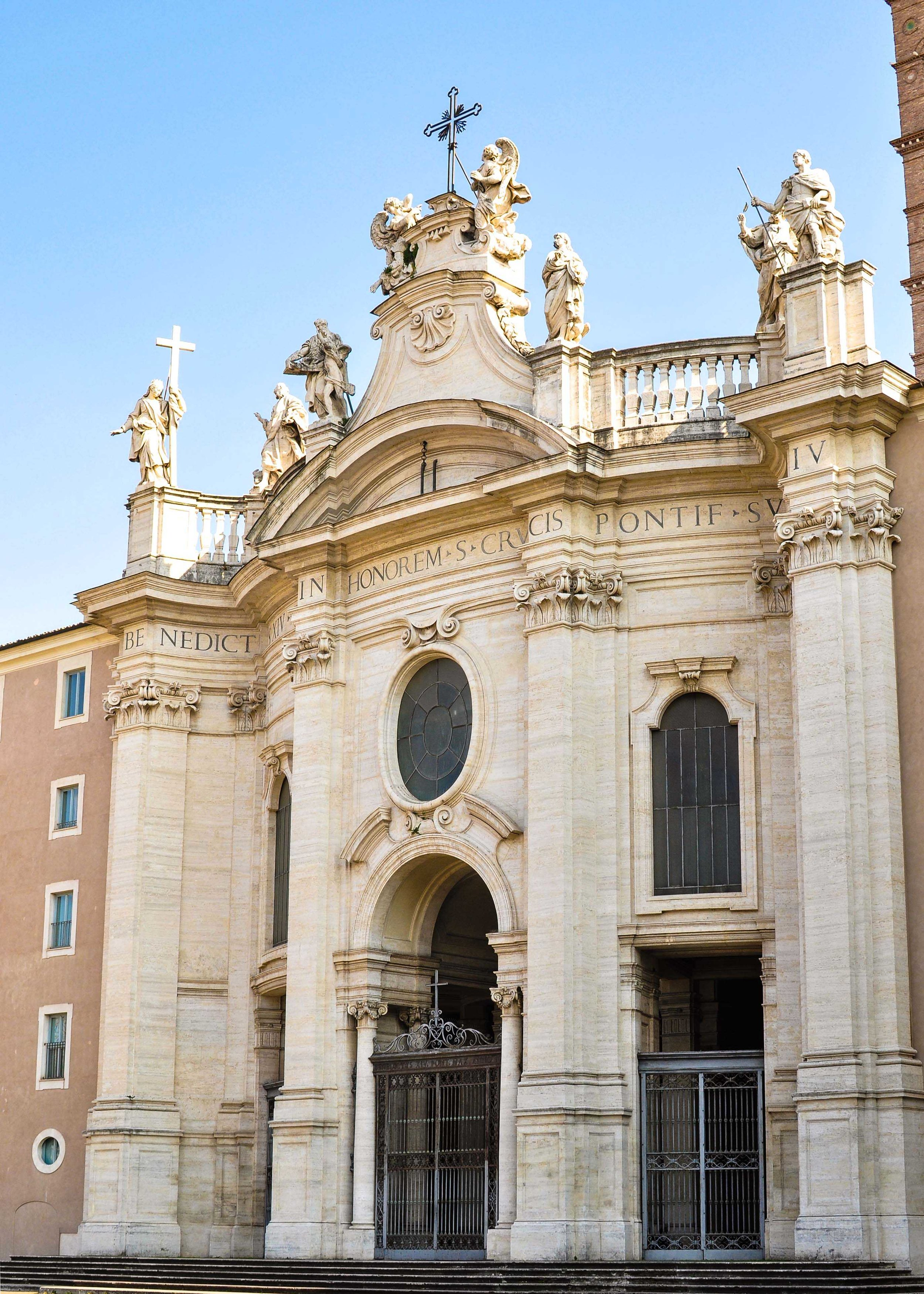 Facade of S. Croce in Gerusalemme, Rome.  The church is called Basilica of the Holy Cross in Jerusalem because at one time the floor was covered with dirt from Jerusalem so that the Holy Land would be a part of the foundation. The statue on the far left holding the cross is St. Helena and she is mirrored by a statue of her son, Constantine.