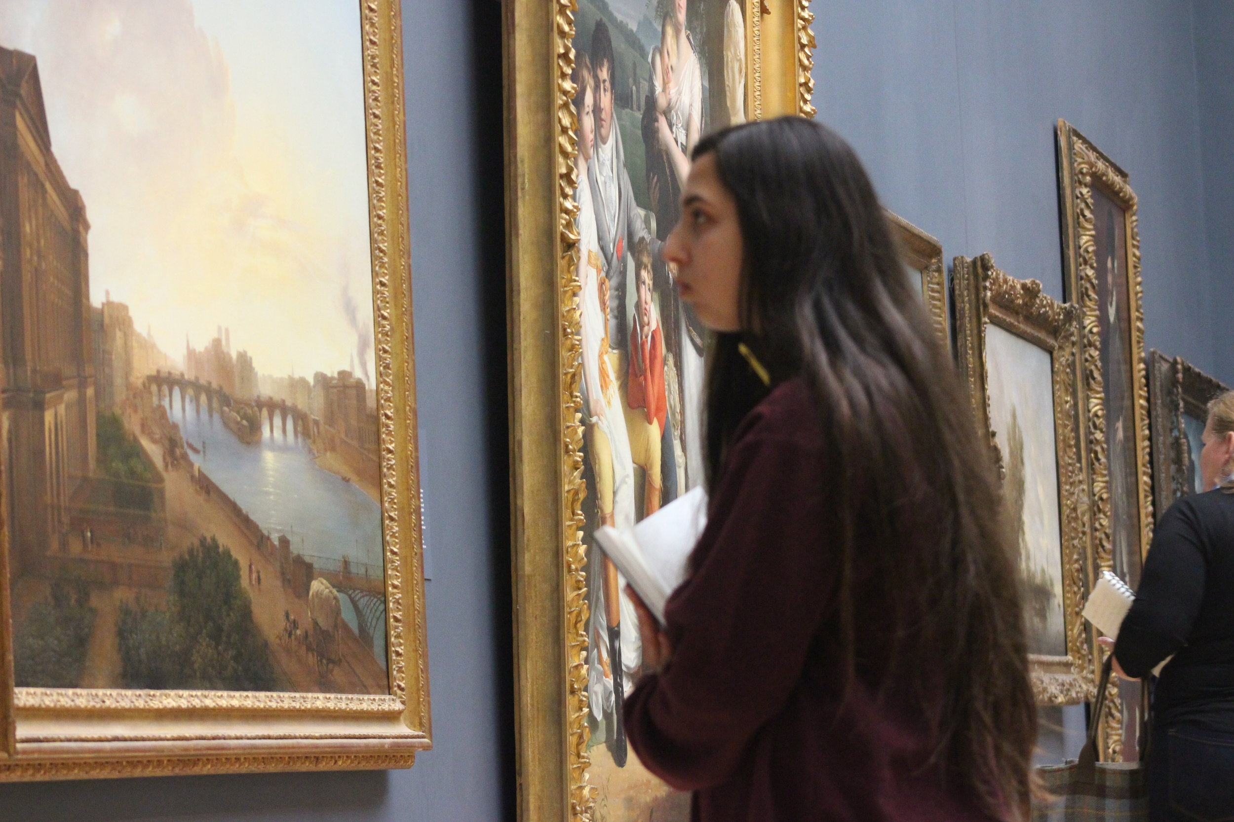 A student in deep concentration while observing a painting
