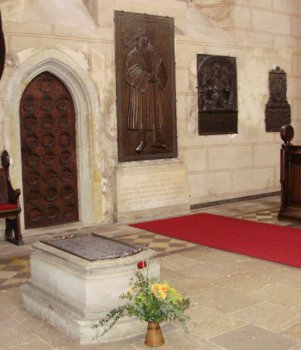 Luther's grave and memorial plaque in Wittenberg with other plaques next to his