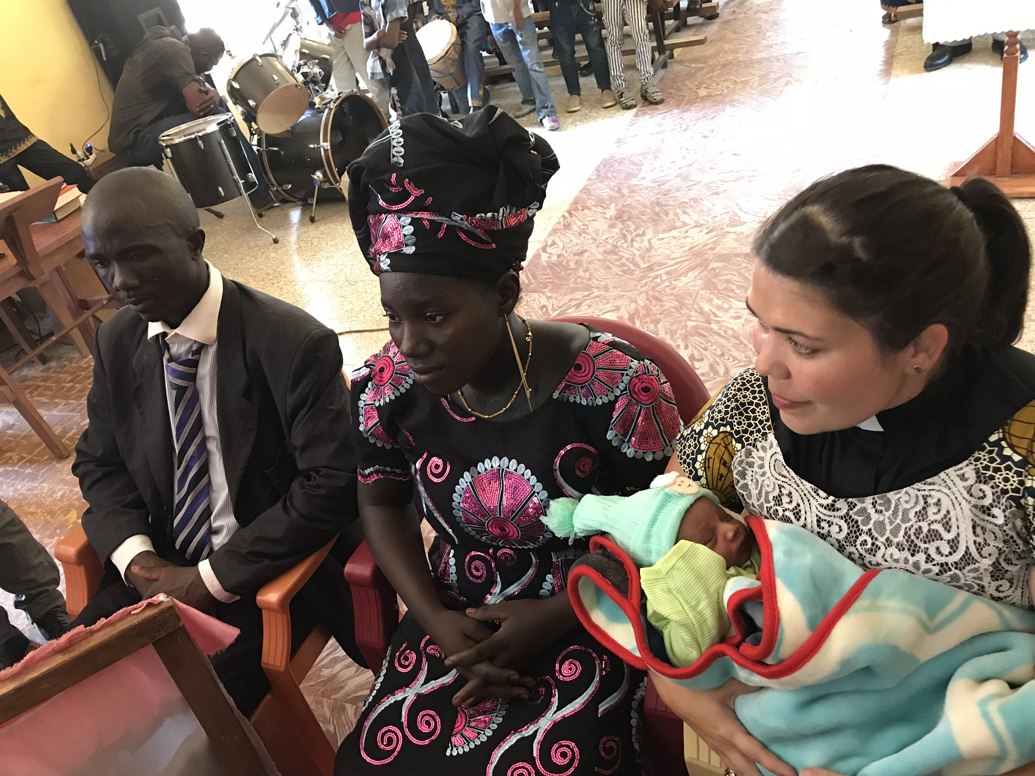 """The time came for the naming. After the people came forward to give their financial gifts to the family, the pastor named the child """"Rev. Katherine Meek Kaingbanja"""". Then they had me go sit next to them and handed her to me. As I held her people came forward to pray over her prophetic words of blessing. It was emotional."""