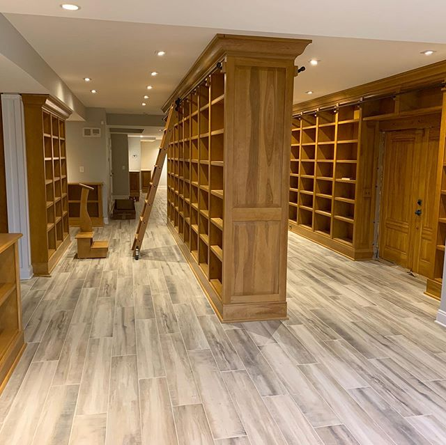 Pictures of a #homelibrary project with 55 floor-to-ceiling #bookcase units for over 970 feet of #bookshelf space with rolling #libraryladder and #raisedpanel details.  #library