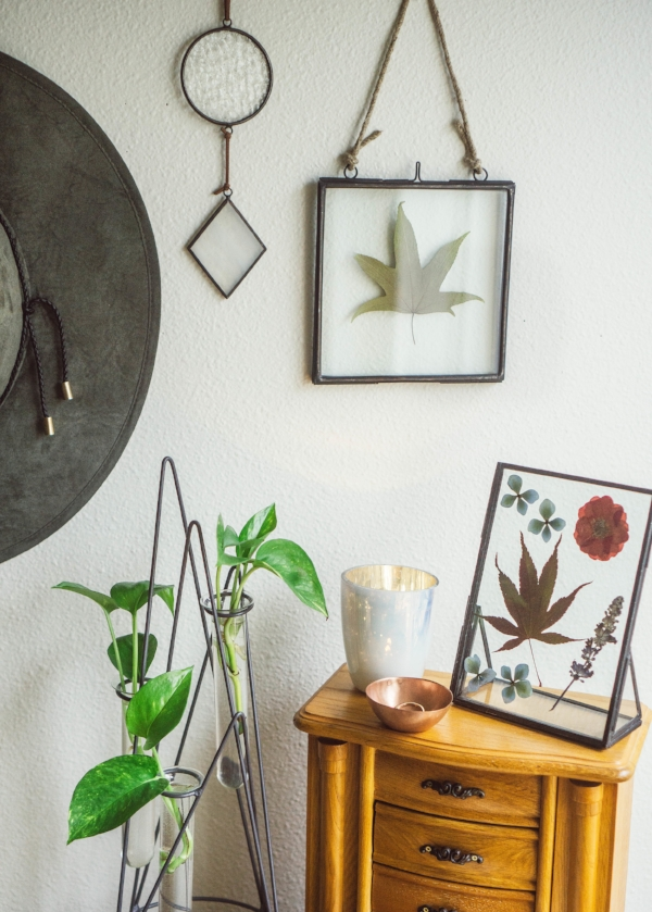 pressed flowers and leaves in hanging glass frame in boho style bedroom