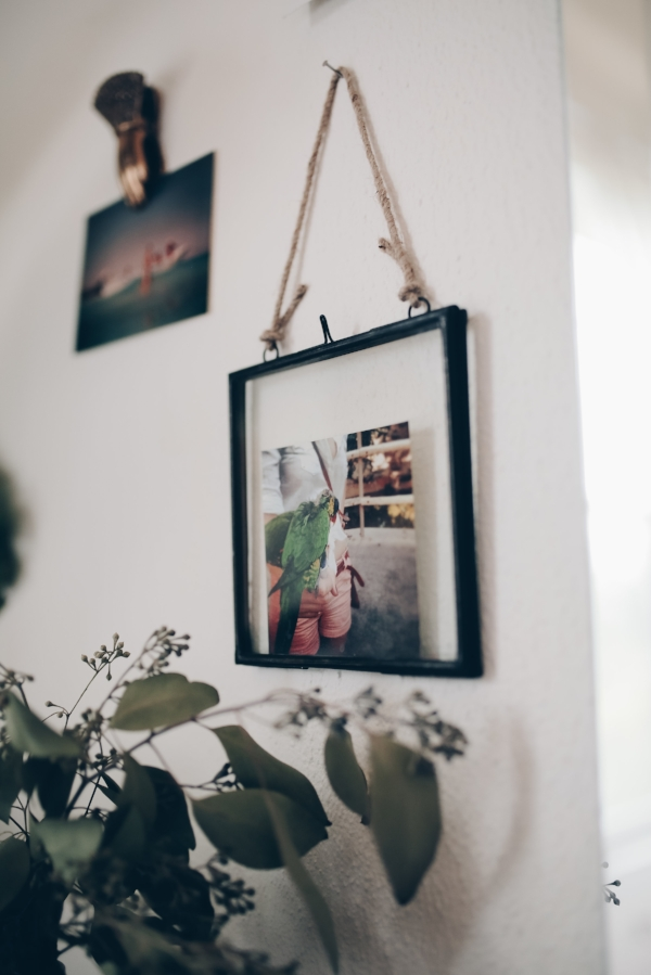 Metal and glass hanging frame with polaroid photos in bohemian chic bedroom