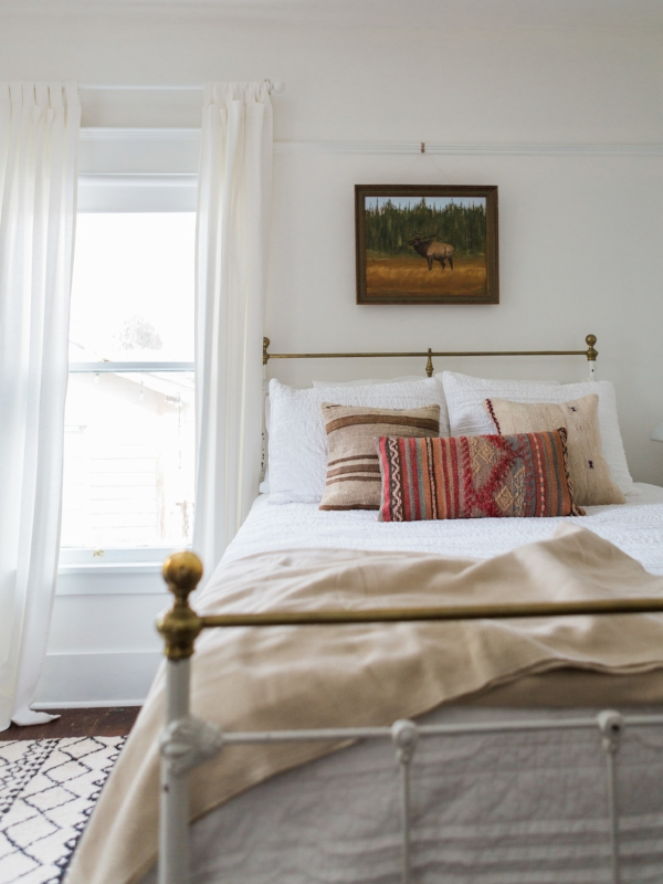 All white bedroom with vintage charm and bohemian kilim pillows at Foraged Home