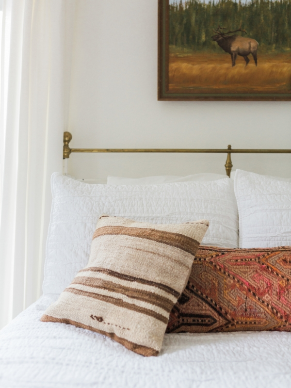 Square kilim pillows for white bedspread in bohemian and vintage style bedroom from Foragedhome.com