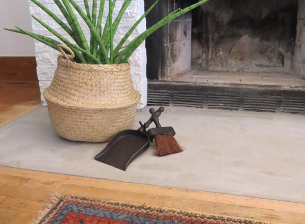 basket as a plant stand  and a small cast iron broom and dustpan in a fireplace cozy setting at Foraged Home