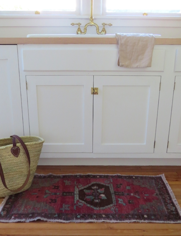 All white kitchen and small Turkish Kilim rug for in front of the sink from Foragedhome.com