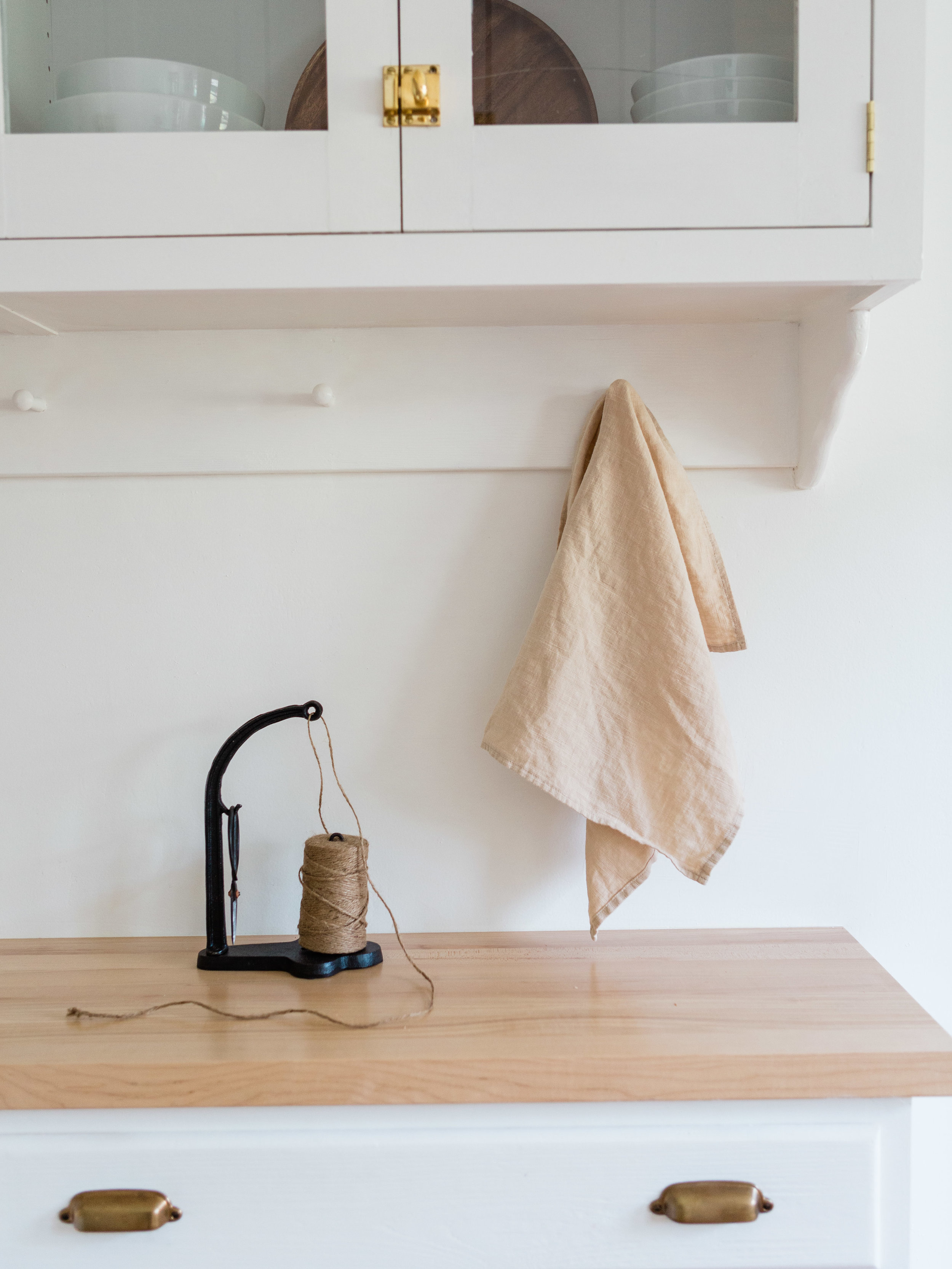 All white kitchen with butcher block counter tops and peg rack Foraged Home