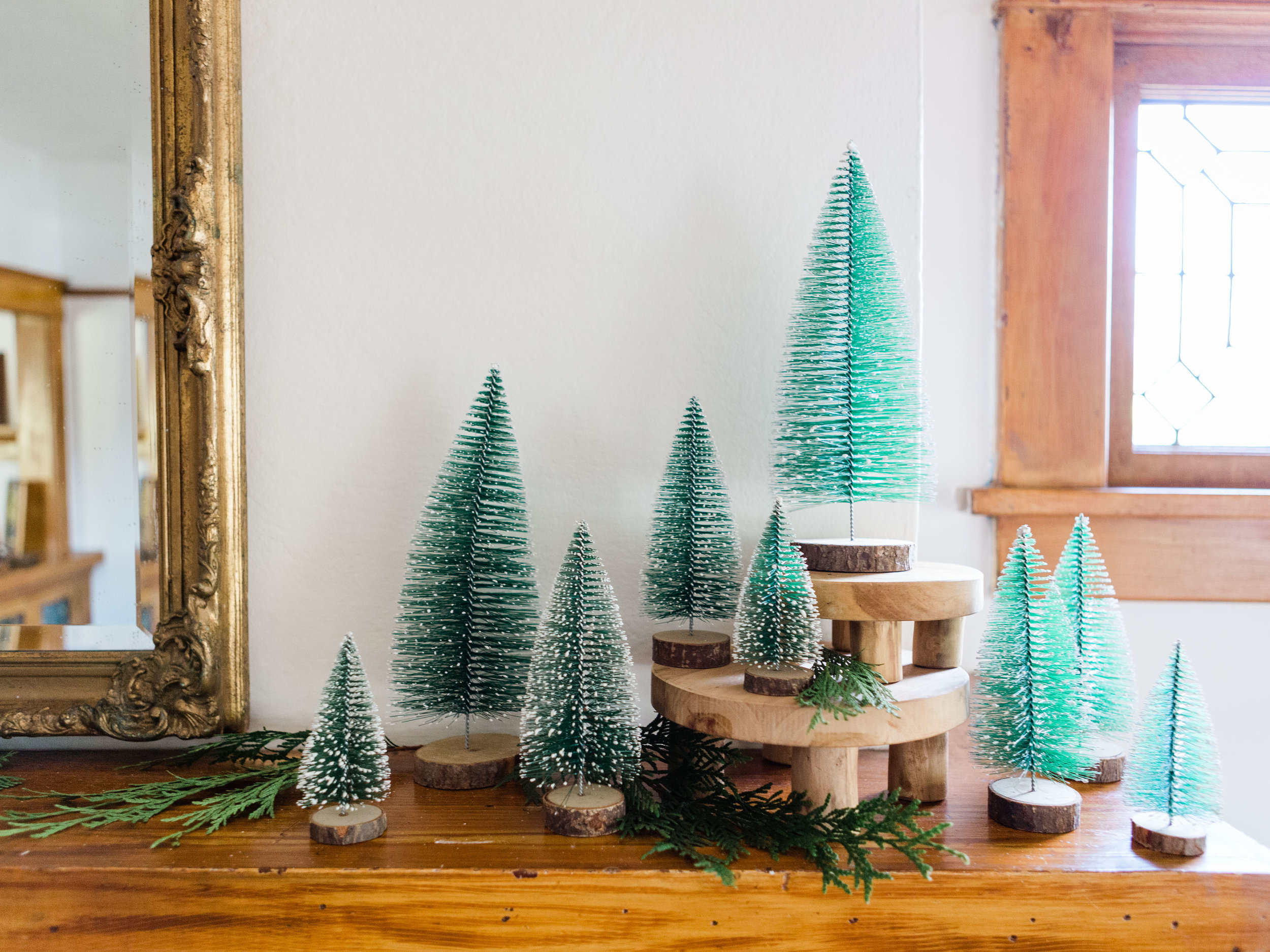 Bottle brush trees on holiday mantle from Foragedhome.com