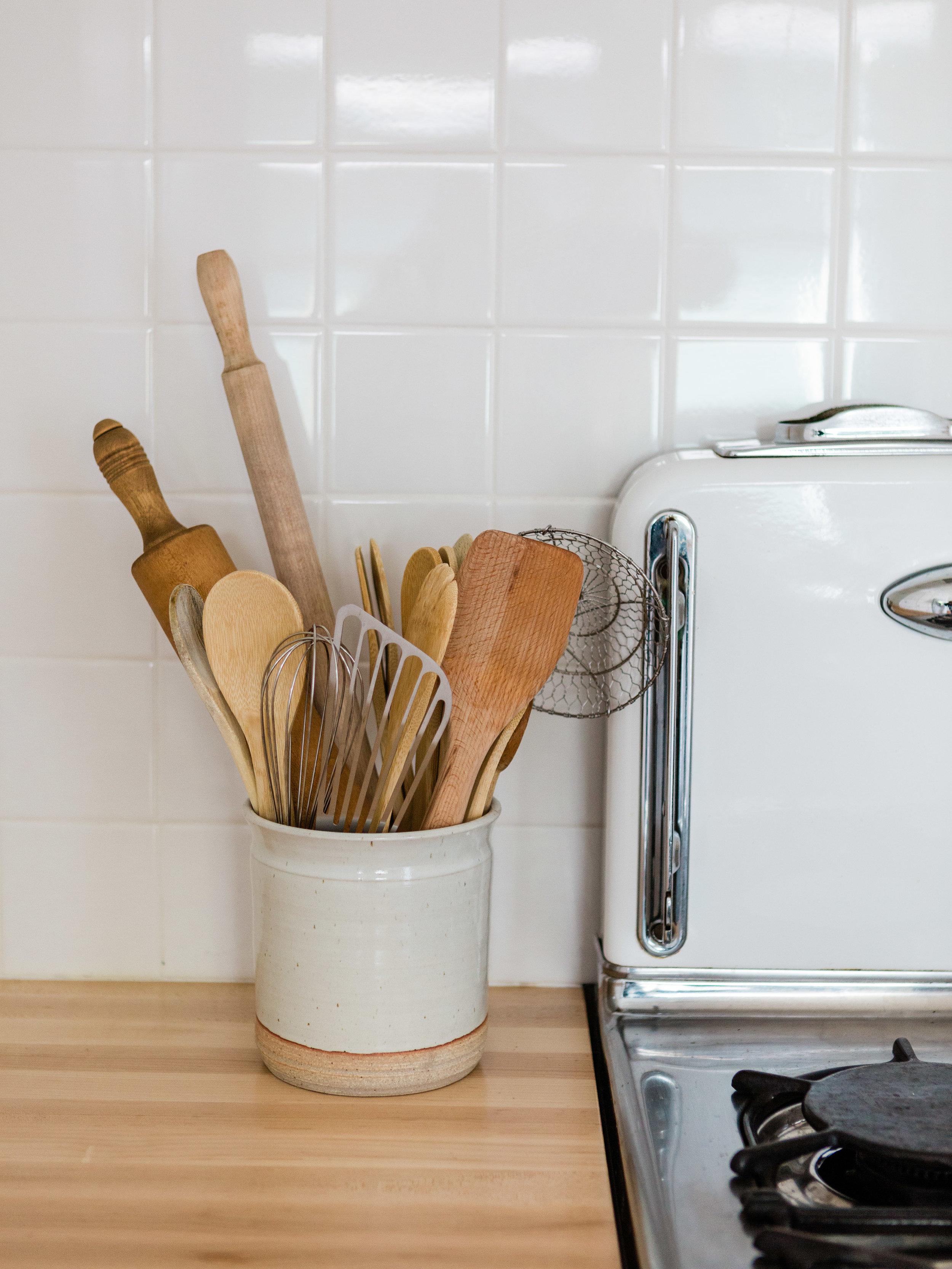 Ceramic handmade utensil holder in white kitchen from Foragedhome.com