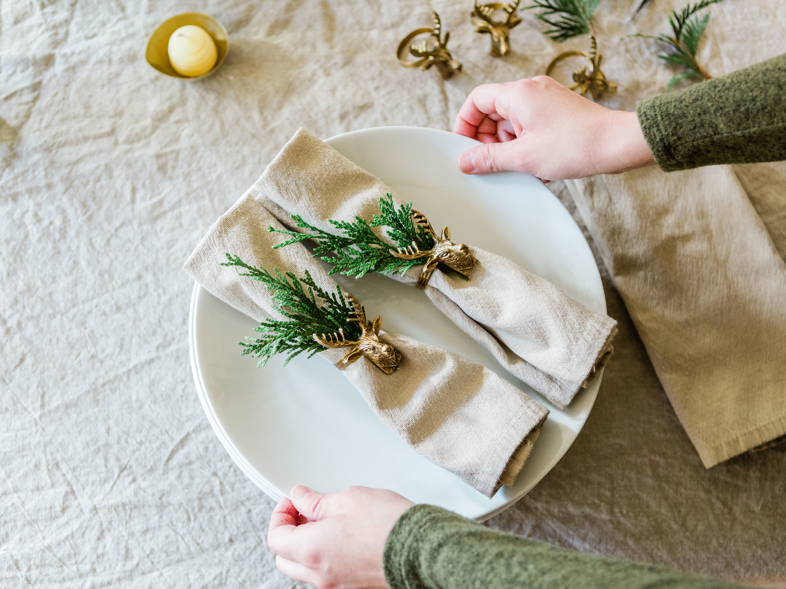 Simple and beautiful holiday place setting with greenery and brass deer napkin tags from Foraged Home