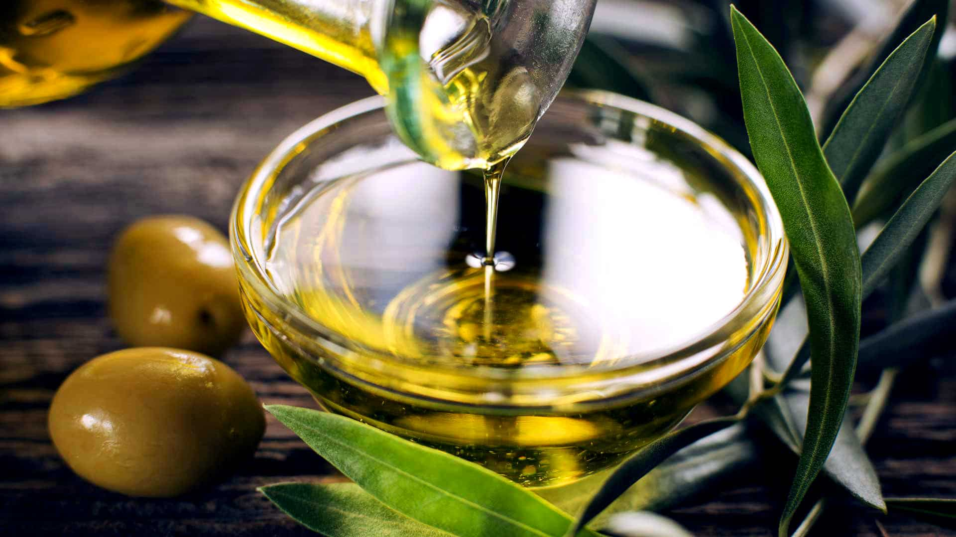 pouring olive oil in a glass cup