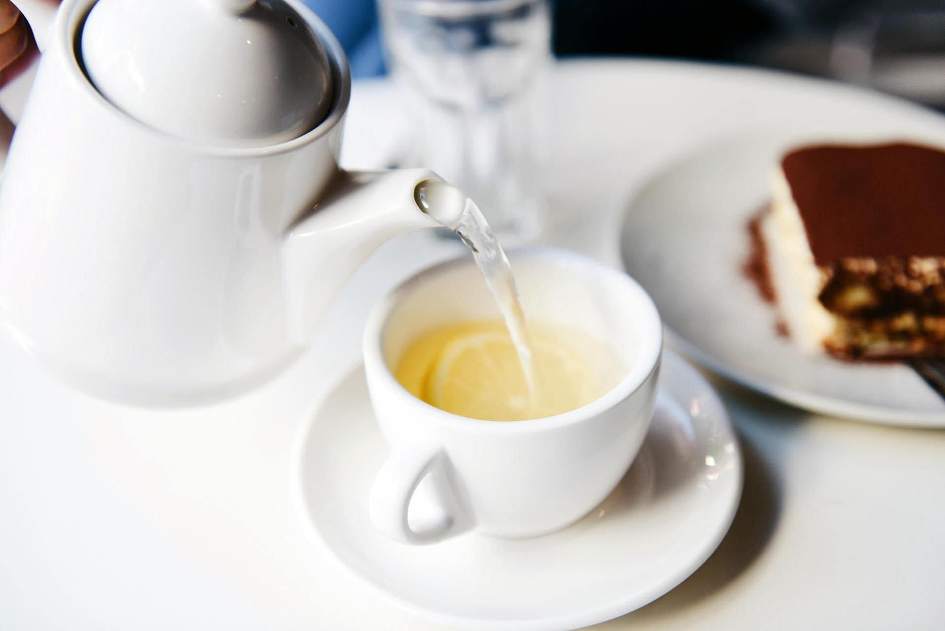 pouring white tea in ceramic cup