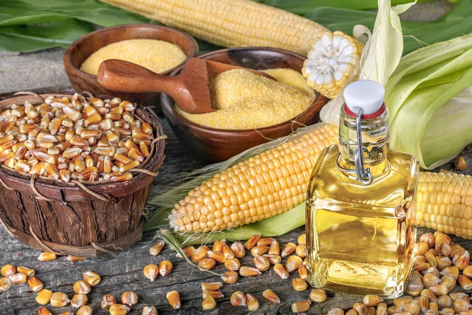 corn oil and dried corn kernels on a wooden table
