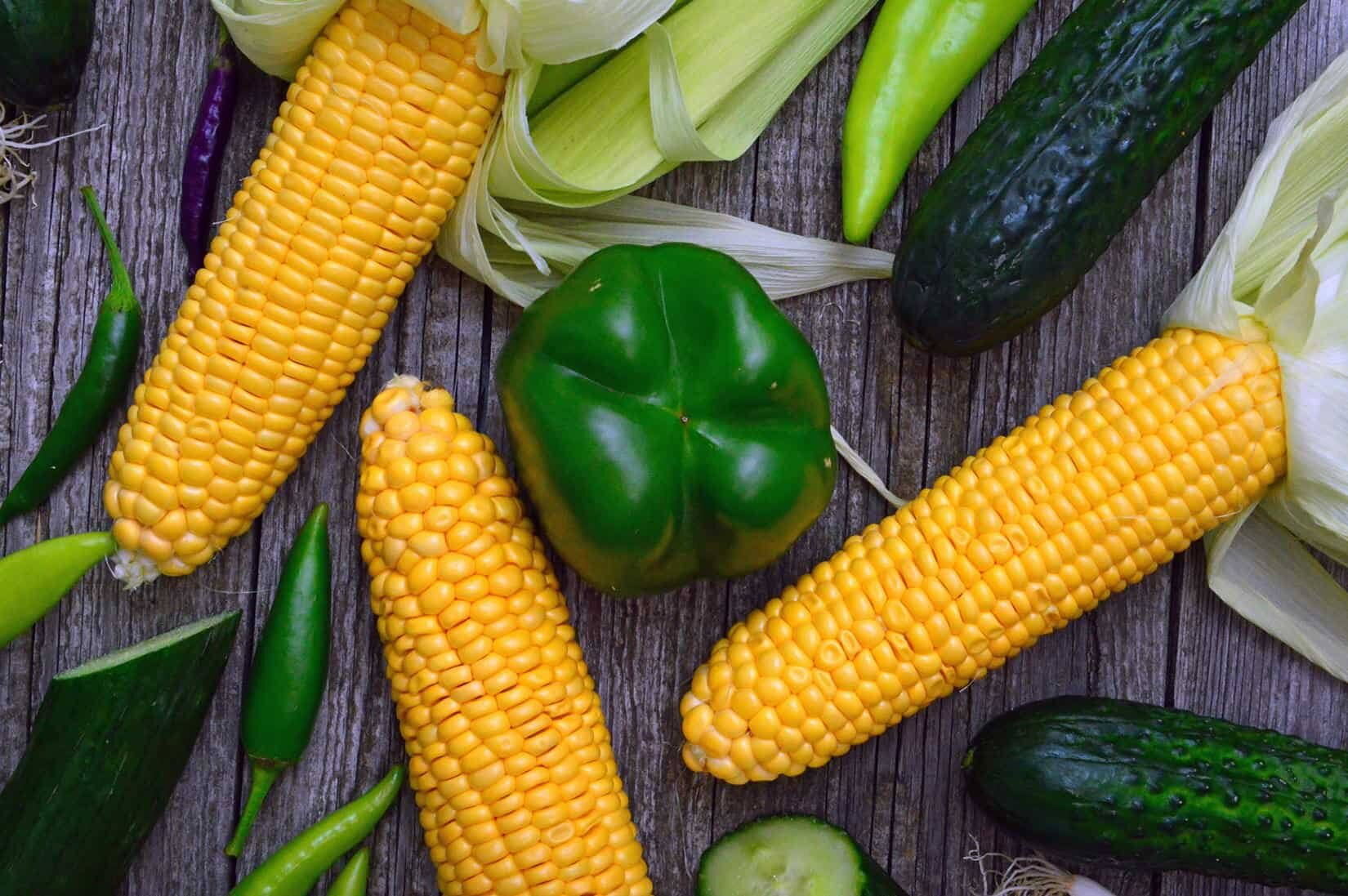 corn on the cob and green peppers on a table