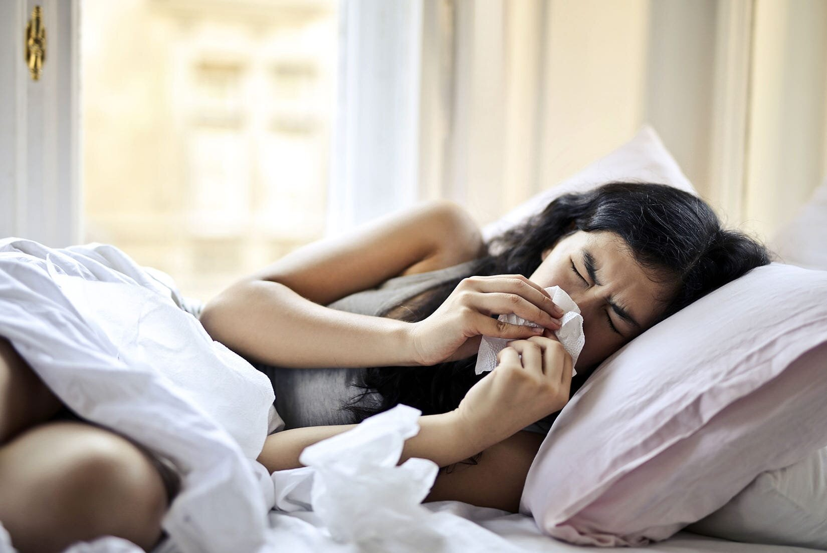 woman lying on bed while blowing her nose hay fever