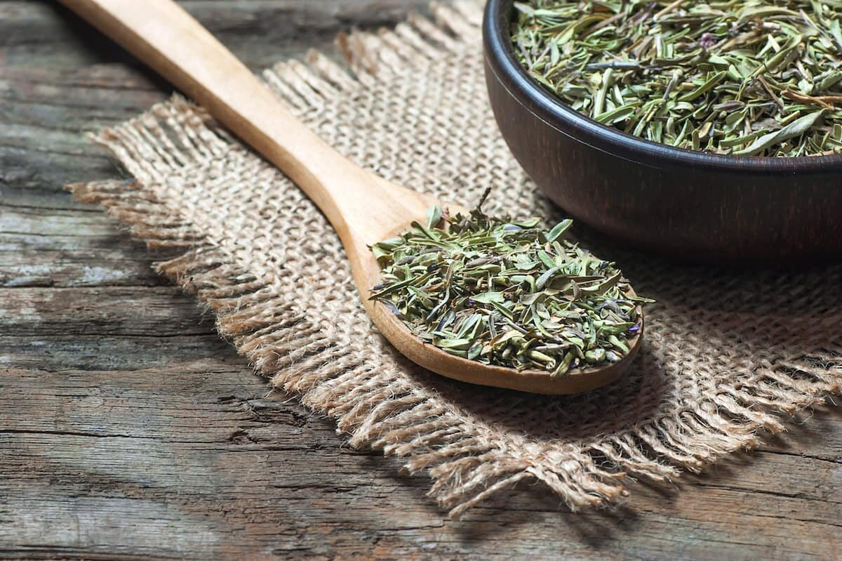 wooden spoon with dried thyme leaves