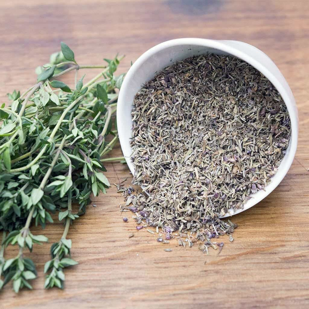 sprigs of thyme branches and a bowl of dried thyme