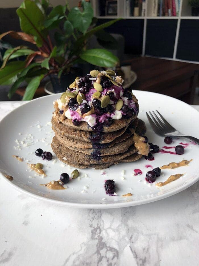 healthy fluffy buttermilk buckwheat pancakes topped with toasted almonds and coconut