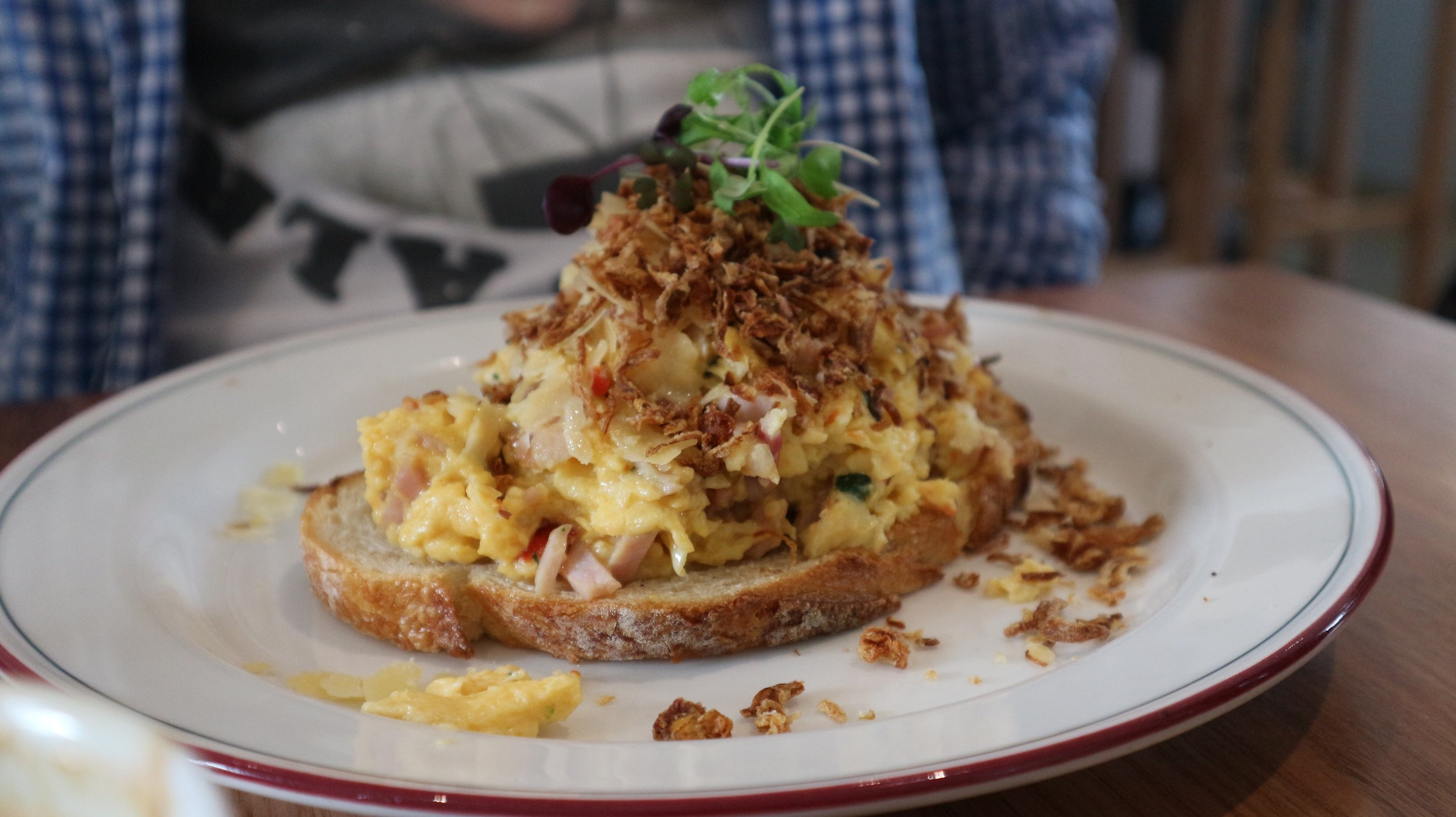 Chilli Scrambled Eggs - with coriander, bacon, cherry tomatoes, Vietnamese mint, fried shallots, & parmesan on sourdough
