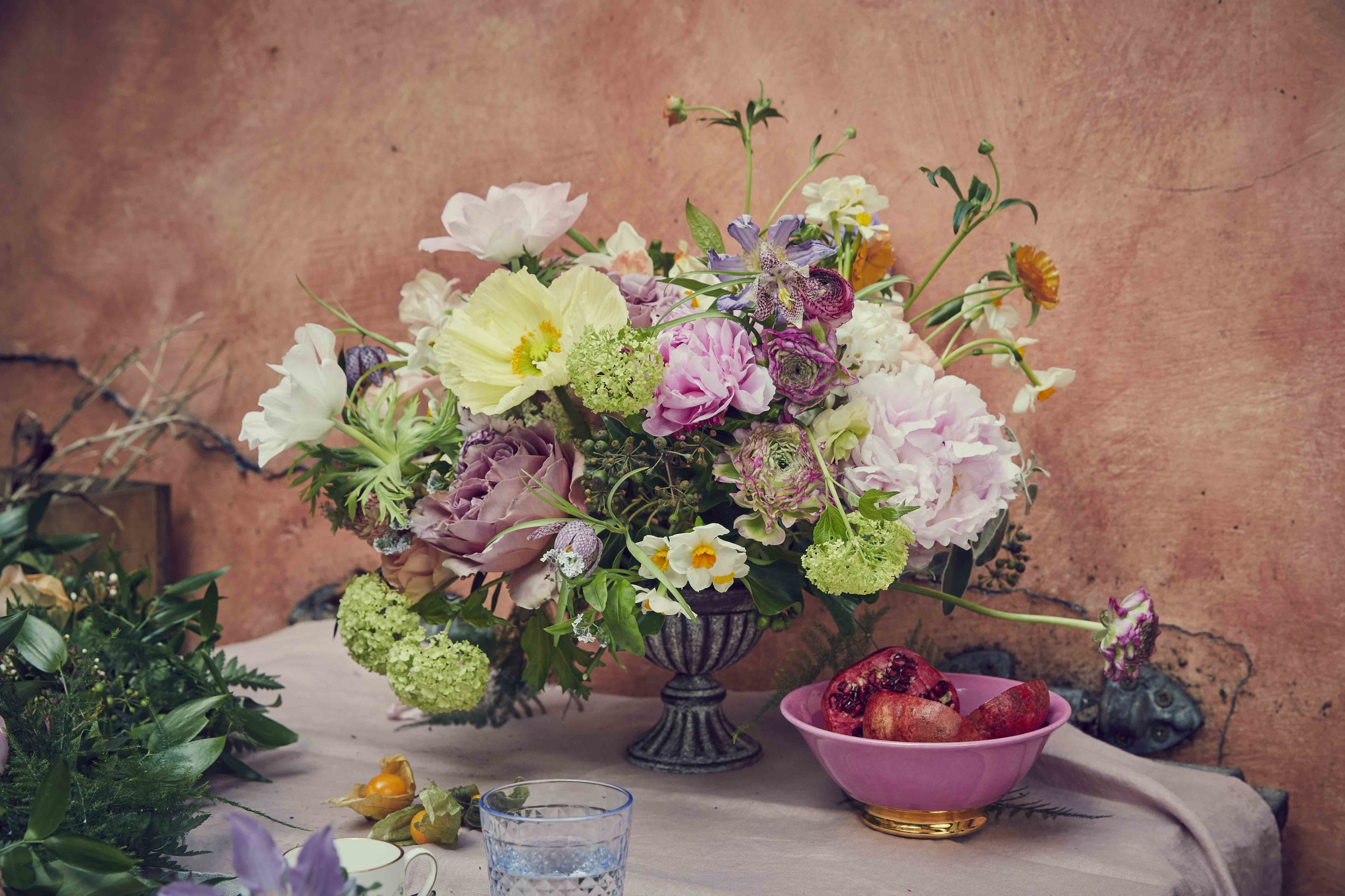 """Above: A compote vessel that holds an arrangement of cloni and butterfly rannunculus, daffodils, poppies, """"Sarah Bernhardt"""" peonies and """"Cafe Latte"""" roses.  Below: Rowan's floral candlestick and showstopper urn featuring delphiniums, pink tuberose, sea lavender, roses and snapdragons; floral garnishes for summer drinks and a flowery cake stand; a large pickle jar filled with larkspur, lisianthus, delphiniums and """"Quicksand"""" roses and Rowan's pressed flower cards."""