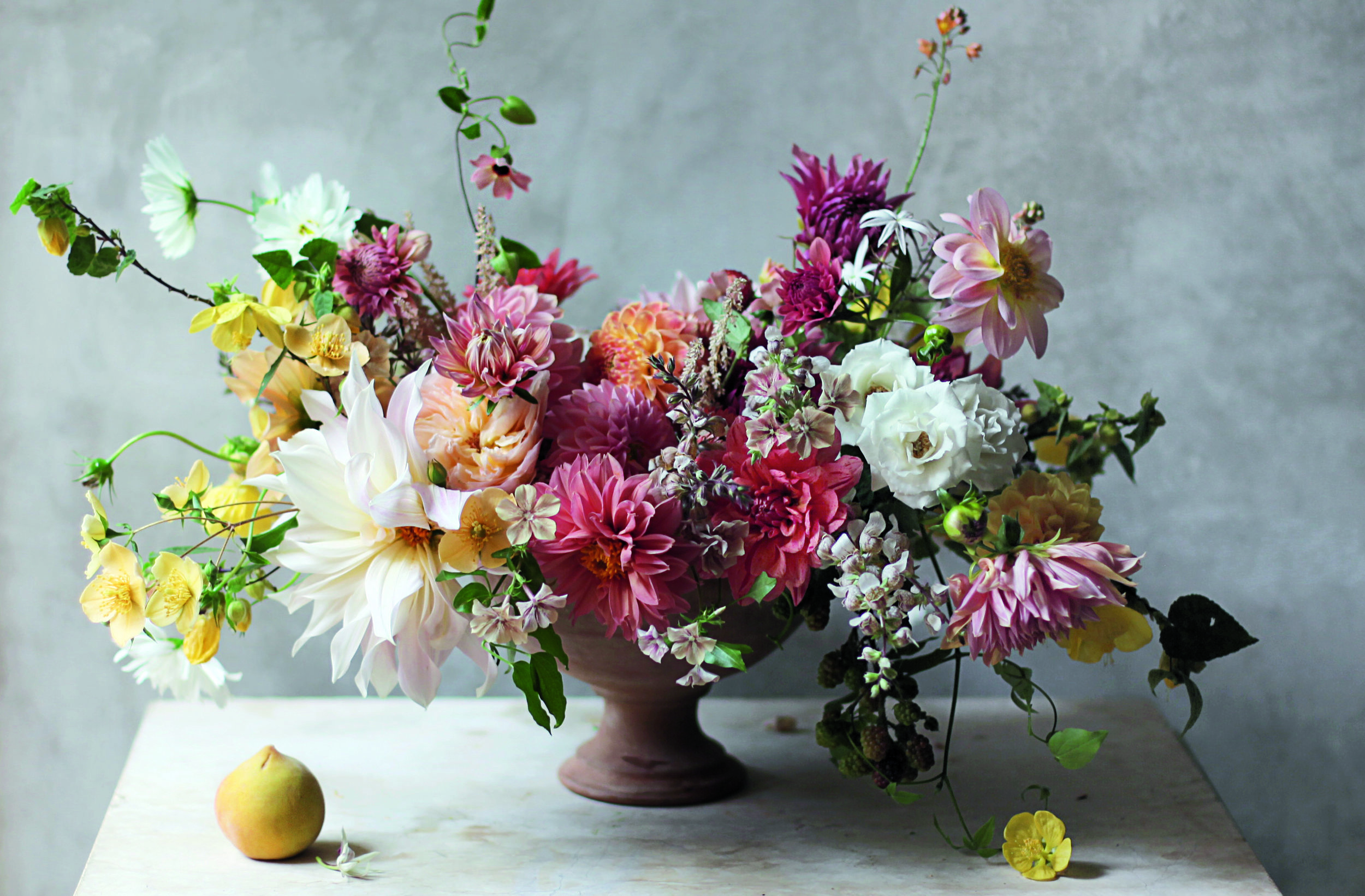 Above: La Musa de las Flores (Gabriela Salazar, Valle de Bravo, Mexico): Centrepiece using dahlias from La Musa's garden. Courtesy La Musa de las Flores. Below: Petalon (Florence Kennedy, London): hanging arrangement made with students at a Petalon workshop, using lavatera seed pods, smoke bush, hydrangea 'Limelight' and 'Kyushu', and hellebore 'Winterbells'. Picture courtesy of Petalon; Matagalán Plantae (Carolina Spencer, Barcelona): from the 'Totem' series, 2017, vase by Matagalán with anthurium, agapanthus, alliums, echinacea, calathea leaf and red-hot pokers. Picture credit: courtesy Matagalán Plantae/ Florencia Lucia; Frida Kim Flowers (Frida Kim, London): Dancing buttercup flowers with Solomon's seal. Picture: courtesy Frida Kim Flowers; Aesme (Jess Lister and Alex Nutting, London and Hampshire): tablescape using May flowers, including aquilegias, pansies, forget-me-nots, geums, alliums and pale clematis. Picture courtesy of Aesme.