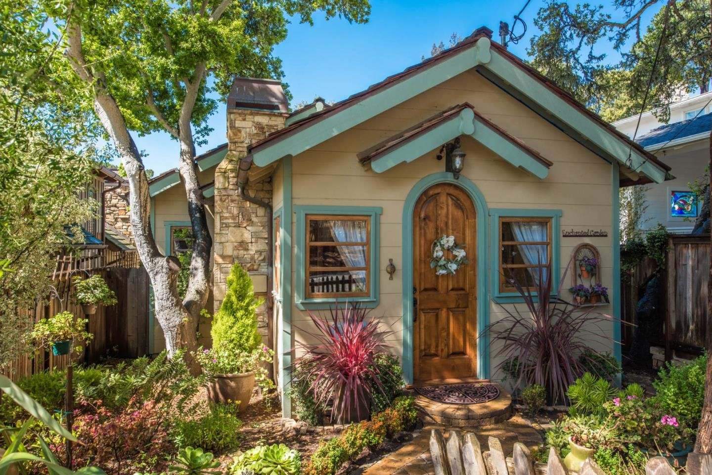 The-most-adorable-cottage-in-Carmel-is-small-with-large-space-Arched-front-door-and-teal-trim..jpg