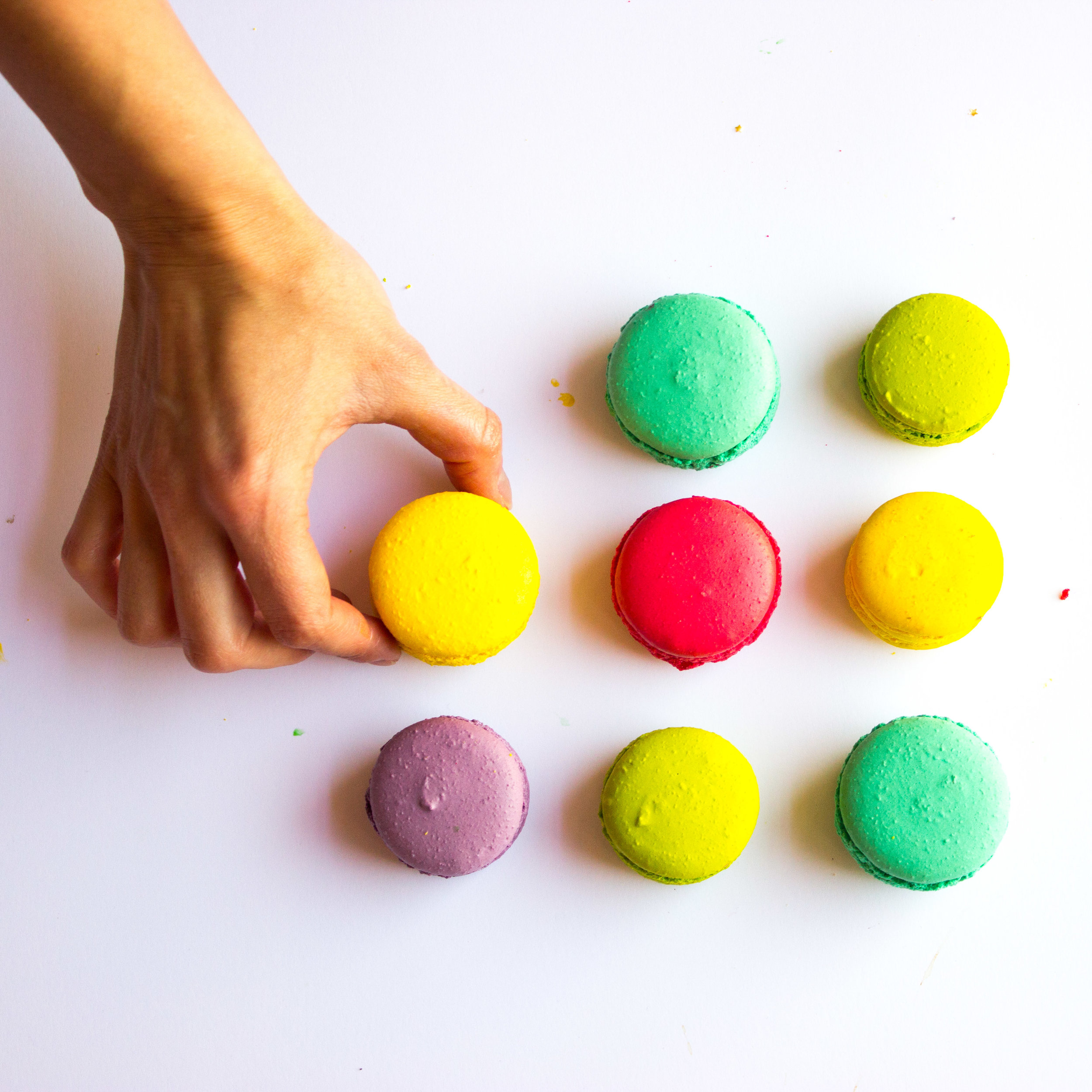 Hand picking coloured macaron.jpg