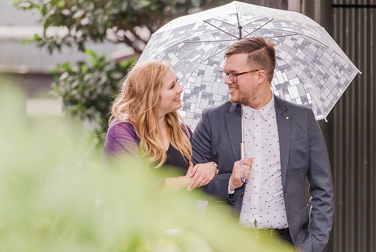 Birmingham Wedding Photographer couple walking while holding umbrella