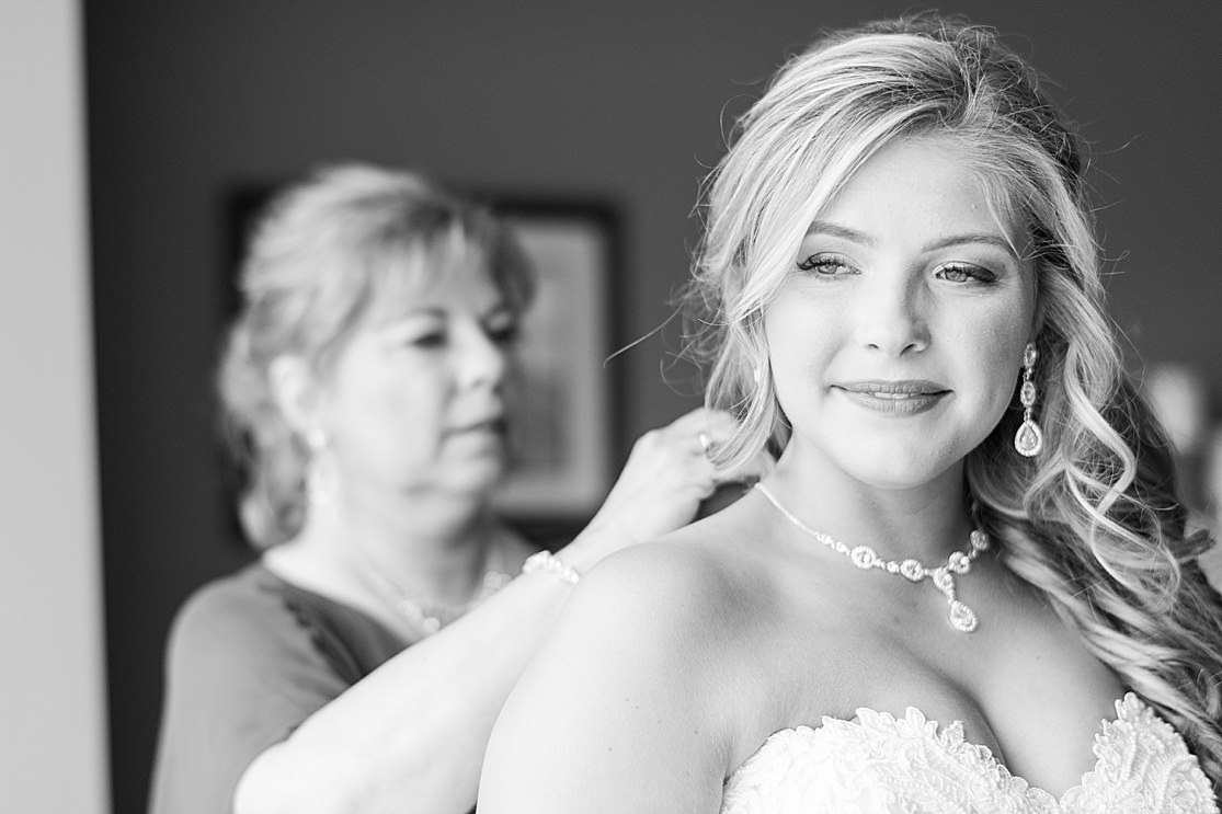 bride and mother of bride putting on necklace in black and white wedding photobridesmaids getting ready taken by west midlands wedding photographer Lisa Lander
