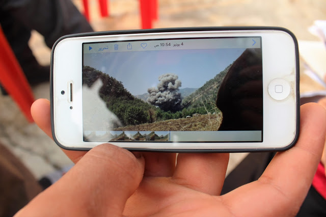 One of the villagers showing the team picture from the last bombing. Photo by: Kasia Protz