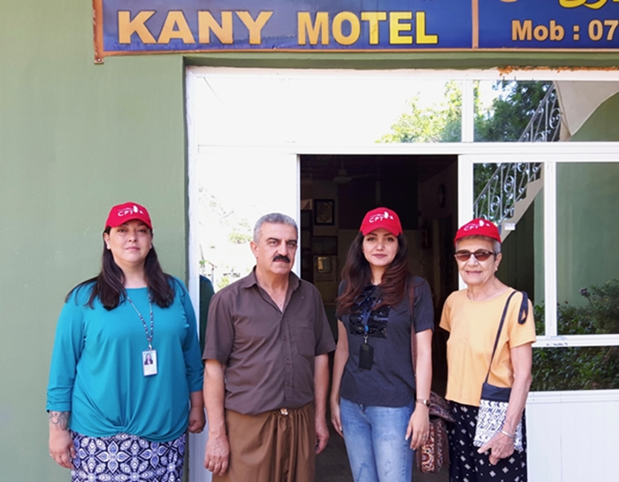 Ayub with the CPT team outside of his motel and tahini factory.