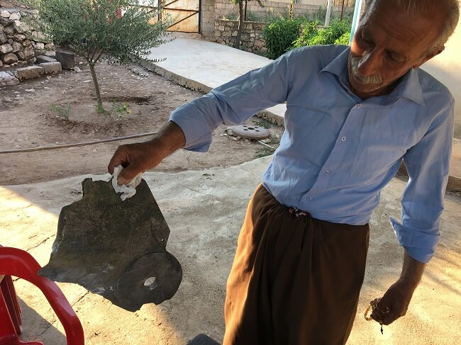 Kak Zaiya, the Mukhtar of the village, showing us a piece of shrapnel from the recent bombardment in Chame Rabatke.