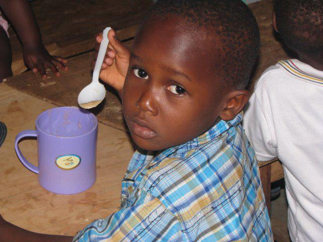 """Without Point Hope's feeding program, this little boy might only have one meal for the entire day--here, he is getting a morning favorite -- """"Tom Brown"""", a local hot porridge."""