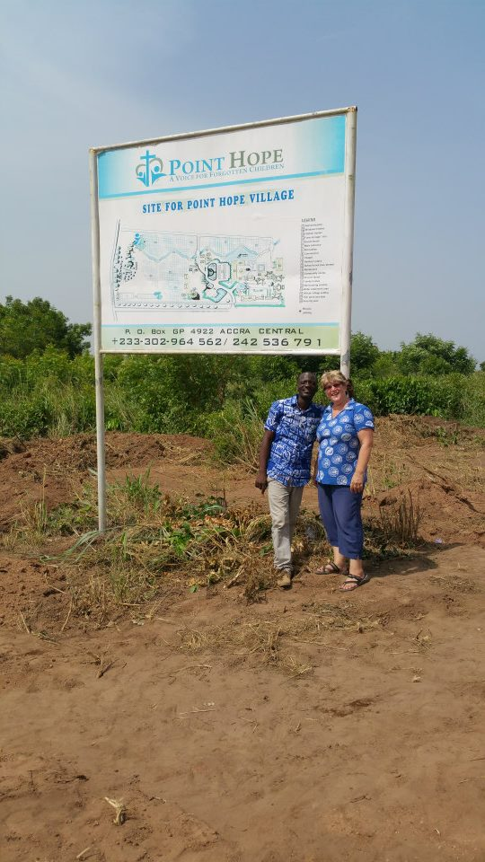 In-Country Director Adam Sandow and Executive Director Jan Haynes stand by the signpost announcing the fact that Point Hope Village is coming soon!