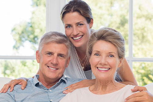 Daugther and two elderly parents smiling