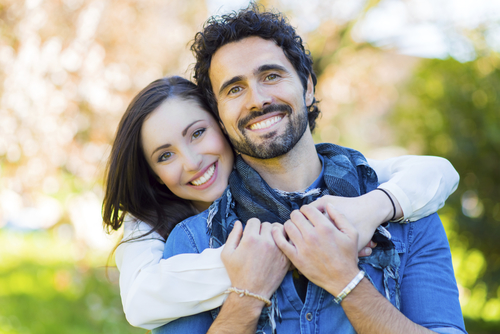 Smiling couple with girl giving man a big hug from behind