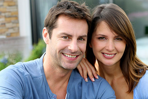 Smiling couple leaning on mans shoulder looking at camera
