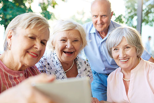Three elderly women and and older man smiling for selfie