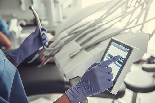 Dental Assistant adjusting settings on dental equipment