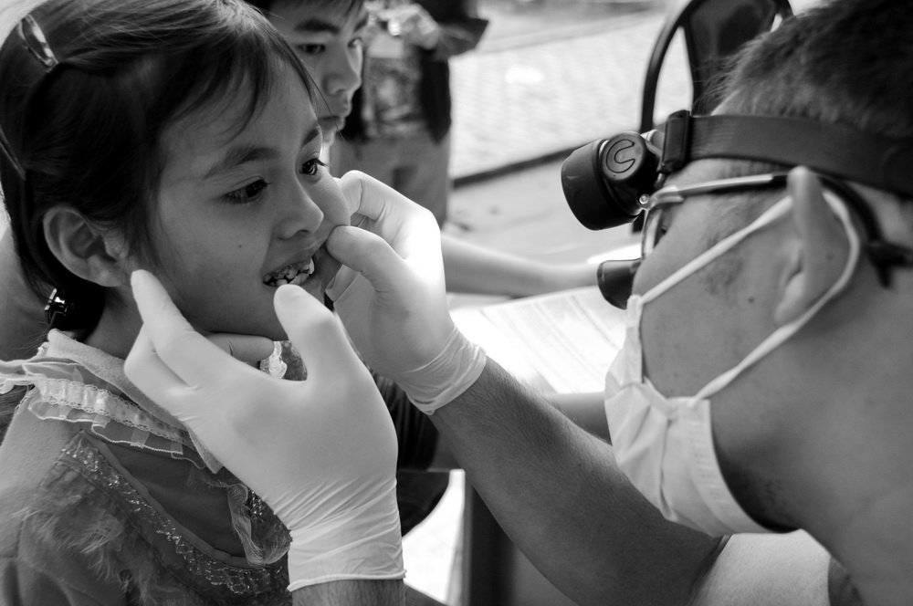 Dr. Nhu inspecting a little girls teeth in Vietnam on a dental relief effort trip.