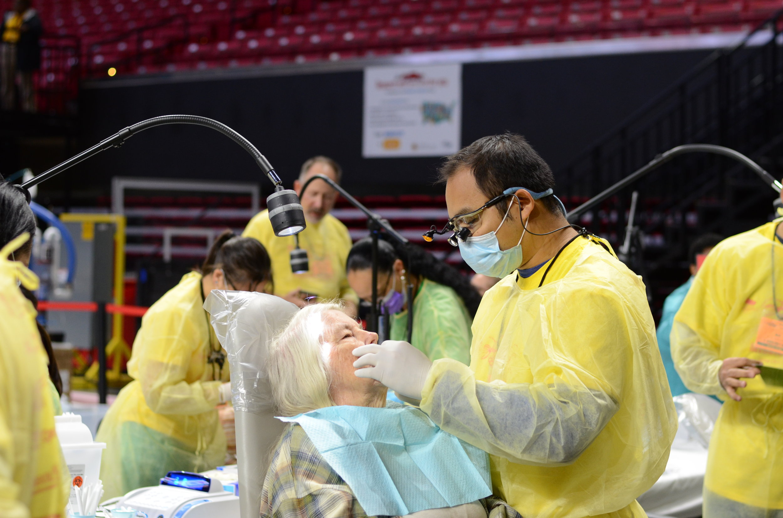 Dr. Nhu assisting a patient at Mission of Mercy 2017.