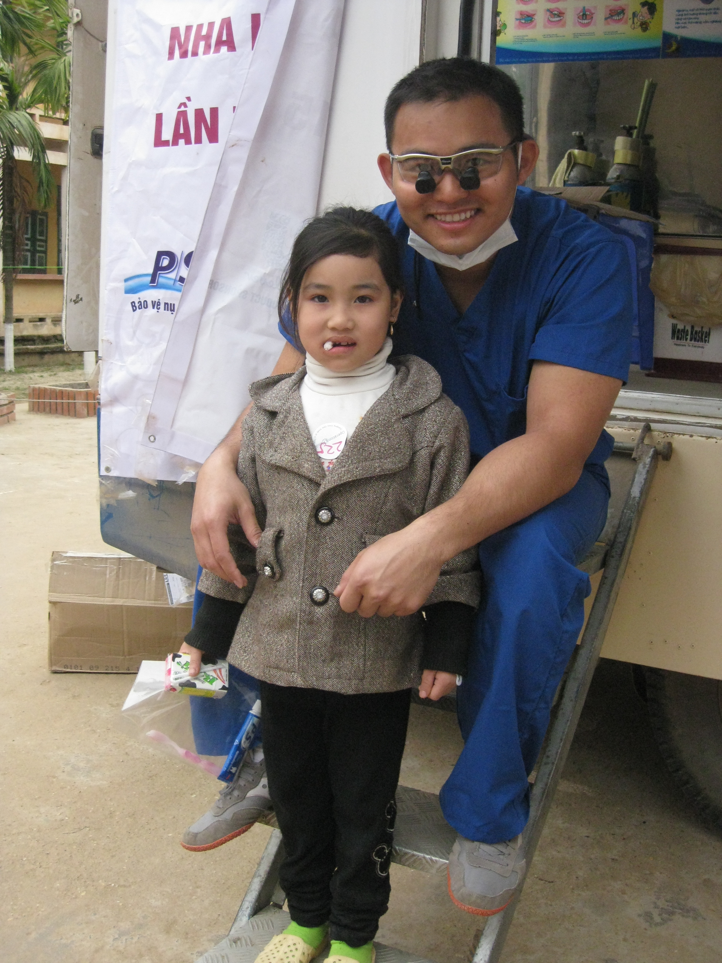 Dr. Tuan Nhu sitting with a little girl after treatment in Vietnam on a dental relief effort trip.