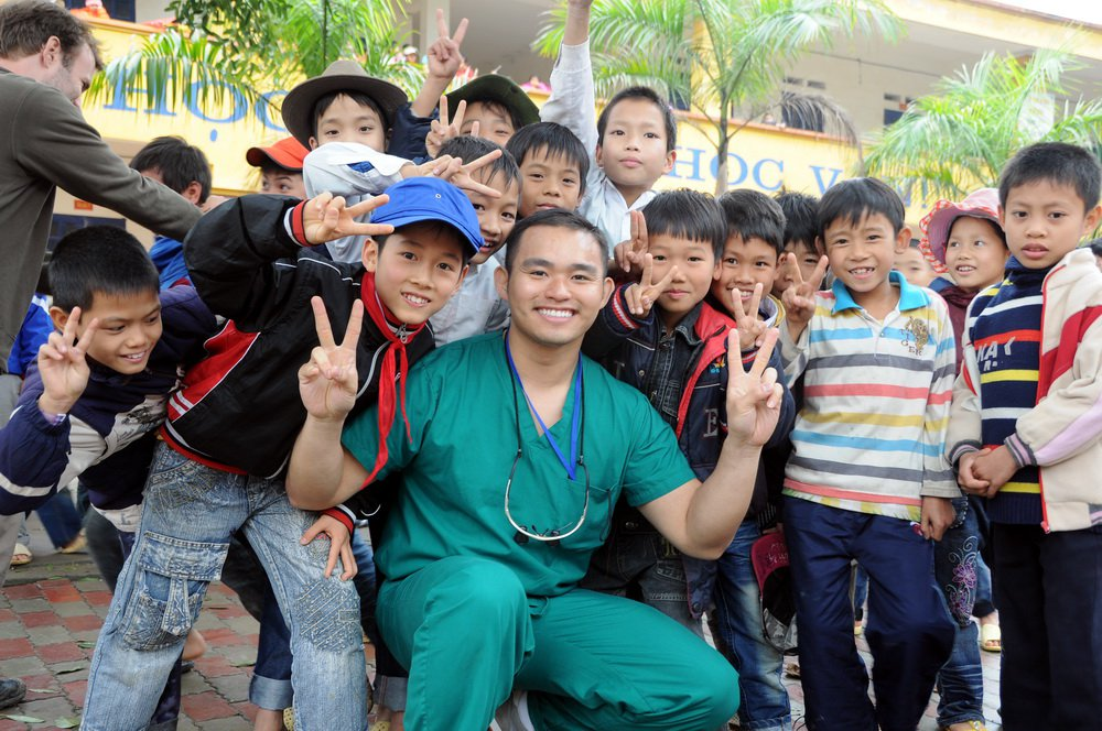 Dr. Nhu smiling with a group of children in Vietnam on a dental relief effort trip.